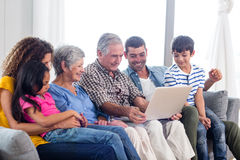 Familia feliz usando la computadora portátil en el sofá Imágenes de archivo libres de regalías