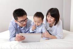 Familia feliz usando la PC de la tablilla Foto de archivo libre de regalías