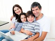 Familia feliz usando una computadora portátil que se sienta en el sofá Imagen de archivo