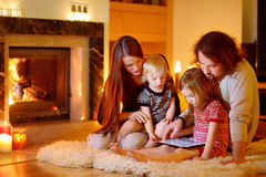 Familia feliz usando una PC de la tableta por una chimenea fotos de archivo