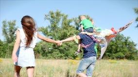 Familia feliz y niñez despreocupada La familia, la mamá, el papá y el hijo felices están caminando en la naturaleza, lanzando una metrajes