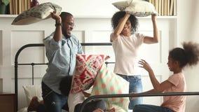 Familia feliz y niños africanos que tienen lucha de almohada en cama almacen de metraje de vídeo