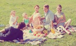 Familia grande amistosa de seis que tiene comida campestre en césped verde en parque Fotos de archivo libres de regalías