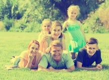 Familia grande con los padres y cuatro niños que mienten en el ou verde del césped Fotos de archivo libres de regalías