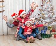Familia grande en los sombreros de santa cerca del árbol de navidad Imagenes de archivo