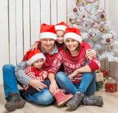Familia grande en los sombreros de santa cerca del árbol de navidad Foto de archivo libre de regalías