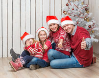 Familia grande en los sombreros de santa cerca del árbol de navidad Imagen de archivo libre de regalías