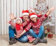 Familia grande en los sombreros de santa cerca del árbol de navidad Foto de archivo