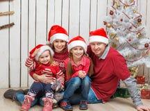 Familia grande en los sombreros de santa cerca del árbol de navidad Fotografía de archivo