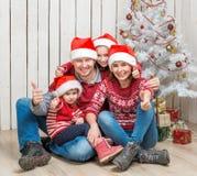 Familia grande en los sombreros rojos de santa cerca del árbol de navidad Fotos de archivo