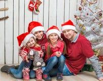 Familia grande en los sombreros rojos de santa cerca del árbol de navidad Imagen de archivo