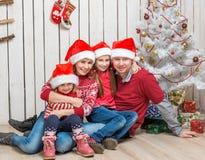 Familia grande en los sombreros rojos de santa cerca del árbol de navidad Fotos de archivo libres de regalías