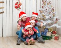Familia grande en los sombreros rojos de santa cerca del árbol de navidad Imagen de archivo libre de regalías