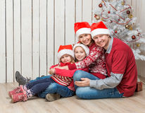 Familia grande en los sombreros rojos de santa cerca del árbol de navidad Imagenes de archivo