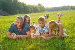 Familia grande en un prado verde foto de archivo