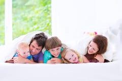 Familia grande feliz en una cama Fotos de archivo