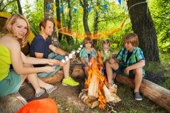 Familia grande feliz que asa a la parrilla las melcochas en palillos foto de archivo libre de regalías