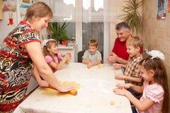 Familia grande feliz que cocina una empanada junto. Imagen de archivo