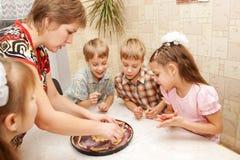 Familia grande feliz que cocina una empanada junto. Imagen de archivo libre de regalías