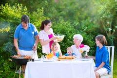 Familia grande feliz que come la carne asada a la parrilla en jardín Imagen de archivo