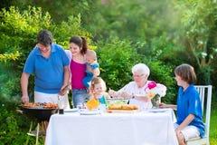 Familia grande que asa a la parrilla la carne para el almuerzo Foto de archivo libre de regalías
