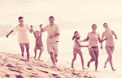 Familia grande que corre en la playa Fotos de archivo libres de regalías
