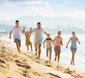 Familia grande que corre en la playa Fotos de archivo