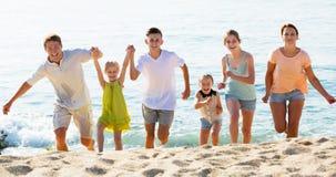 Familia grande que corre en la playa Imagenes de archivo