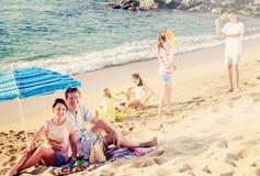 Familia grande que descansa sobre la playa Imágenes de archivo libres de regalías