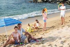 Familia grande que descansa sobre la playa Foto de archivo libre de regalías