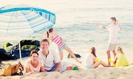 Familia grande que descansa sobre la playa Imagenes de archivo