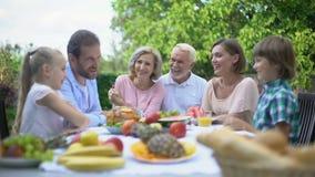 Familia grande que habla durante cena al aire libre, disfrutando del tiempo junto, celebración metrajes