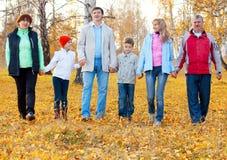 Familia grande que recorre en parque del otoño imagenes de archivo