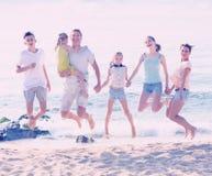 Familia grande que salta en la playa arenosa Fotografía de archivo libre de regalías