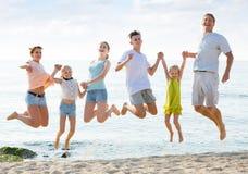 Familia grande que salta en la playa arenosa Fotos de archivo