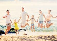 Familia grande que salta para arriba junto en la playa en día de verano claro Fotos de archivo libres de regalías