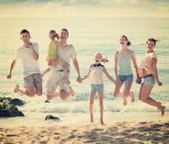 Familia grande que salta para arriba junto en la playa en día de verano claro Imagen de archivo