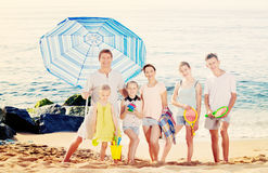 Familia grande que se une en la playa el día de verano Imagen de archivo libre de regalías