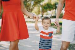 Familia hermosa en rojo que camina abajo de la calle y del parque Fotos de archivo