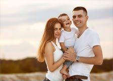 Familia hermosa feliz en la puesta del sol de la playa imagen de archivo libre de regalías