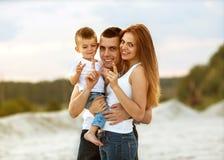 Familia hermosa feliz en la puesta del sol de la playa fotos de archivo