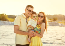 Familia hermosa feliz en la puesta del sol de la playa imágenes de archivo libres de regalías