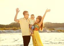 Familia hermosa feliz en la puesta del sol de la playa fotografía de archivo
