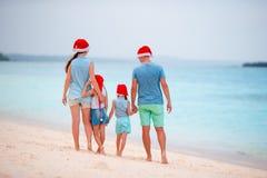 Familia hermosa feliz en los sombreros rojos de Papá Noel en la playa tropical que celebra la Navidad Imagen de archivo
