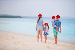 Familia hermosa feliz en los sombreros rojos de Papá Noel en la playa tropical que celebra la Navidad Fotografía de archivo libre de regalías