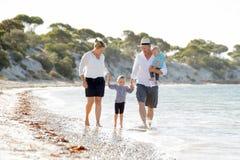 Familia hermosa feliz joven que camina junto en la playa que disfruta de vacaciones de verano Imágenes de archivo libres de regalías