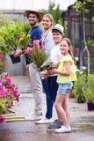 Familia hermosa que mira la cámara mientras que se sostiene florece en el invernadero Foto de archivo libre de regalías