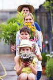 Familia hermosa que mira la cámara mientras que se sostiene florece en el invernadero Fotografía de archivo
