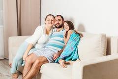 Familia hermosa que se sienta en un sofá en la sala de estar fotos de archivo libres de regalías