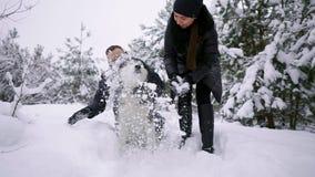 Familia hermosa, un hombre y una muchacha en bosque del invierno con el perro Juego con el husky siberiano del perro almacen de metraje de vídeo
